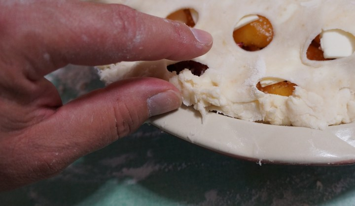 Folding the crust edge back on itself and tucking it under the edge of the assembled pie.
