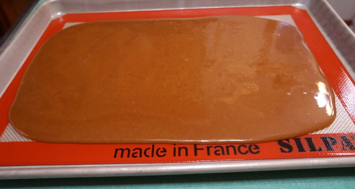 Pour the hot molten toffee into the prepared sheet pan.