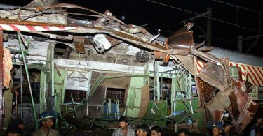 Police and onlookers stand around a mangled commuter train's wagon following a series of blasts which targetted India's financial capital commuters' network in Mumbai, 11 July 2006.  As many as 70 to 80 people were killed and at least 211 injured when blasts rocked commuter trains in India's financial capital during the evening rush hour, police said.