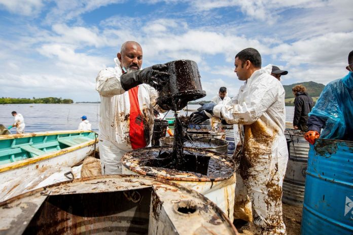 Volunteers cleaning up oil spill at beached near Mauritius