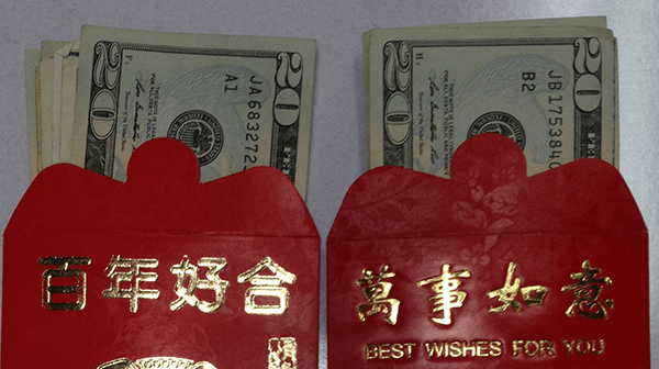 Two red envelopes with Chinese characters on them and stuffed with U.S. dollars.