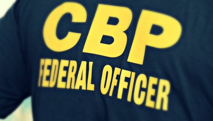 """The back of a CBP officer's shirt reading """"CBP Federal Officer"""" in bold yellow letters."""