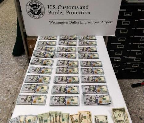 $28k laid out on a white table at Dulles airport CBP
