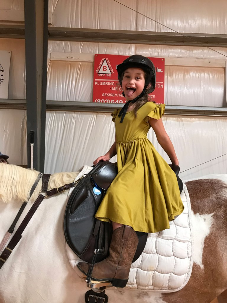image of a happy young rider wearing a yellow dress and smiling