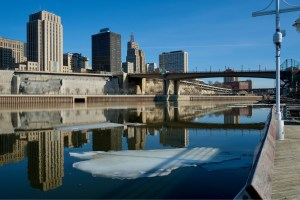 Floating ice on mostly melted Mississippi river, while looking across the riverbank at buildings