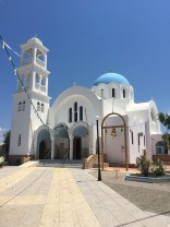 A beautiful Greek Orthodox church behind the beach.