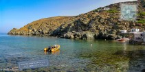 Boat and bathers at cove with clear waters