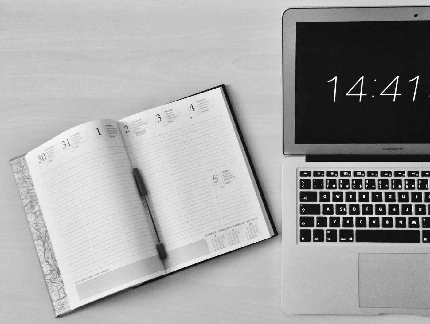 flat lay photography of unfold book beside macbook