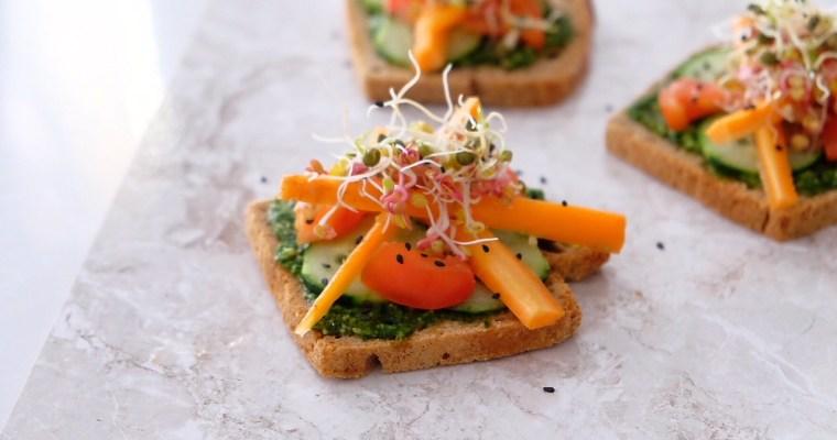 Tostadas con pesto fresco, verduras crudas y germinadas