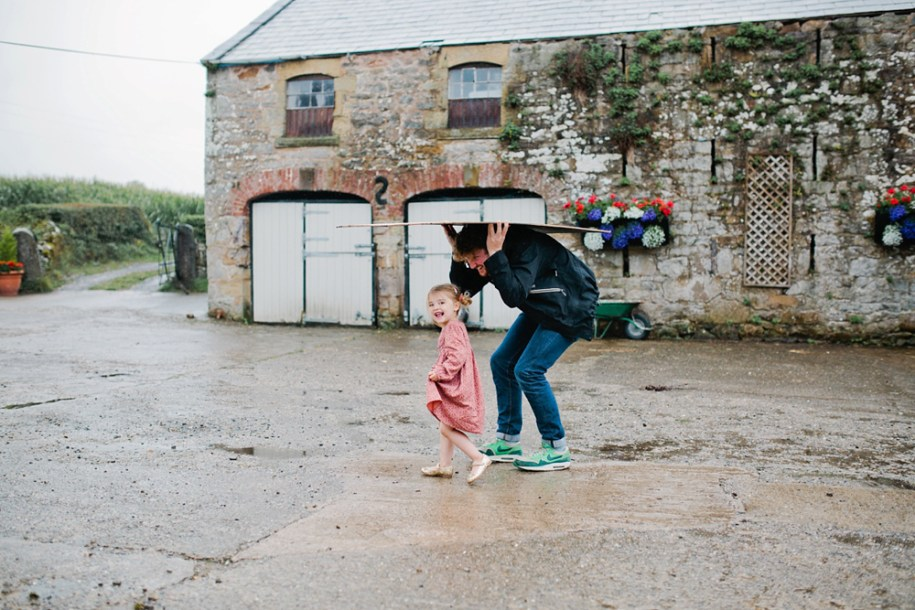 little girl taking cover from the rain by Hawarden wedding photographer