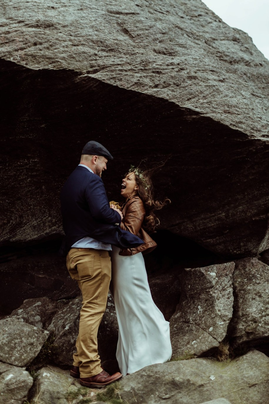 bride and groom laughing and embrace near a rock by Northumberland elopement photographers