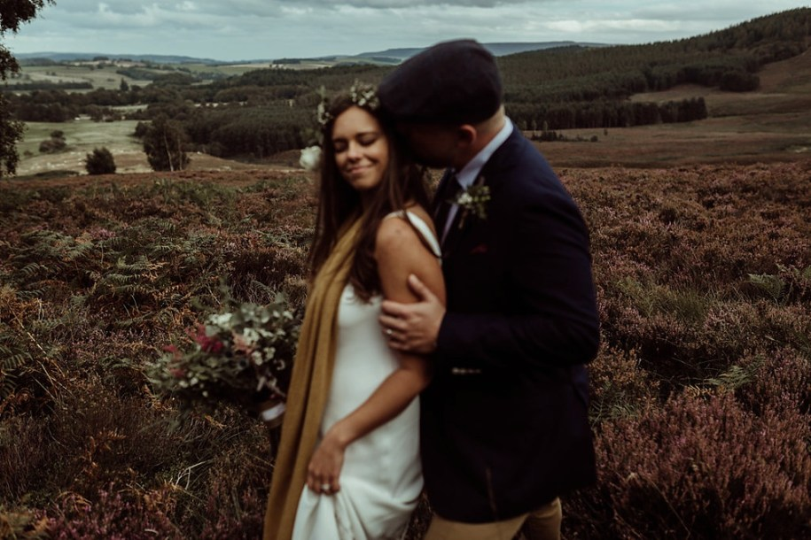 bride and groom holding surrounded by wild heather