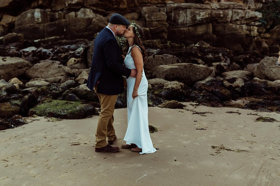 bride and groom kiss for their first look on the beach, near the rocks