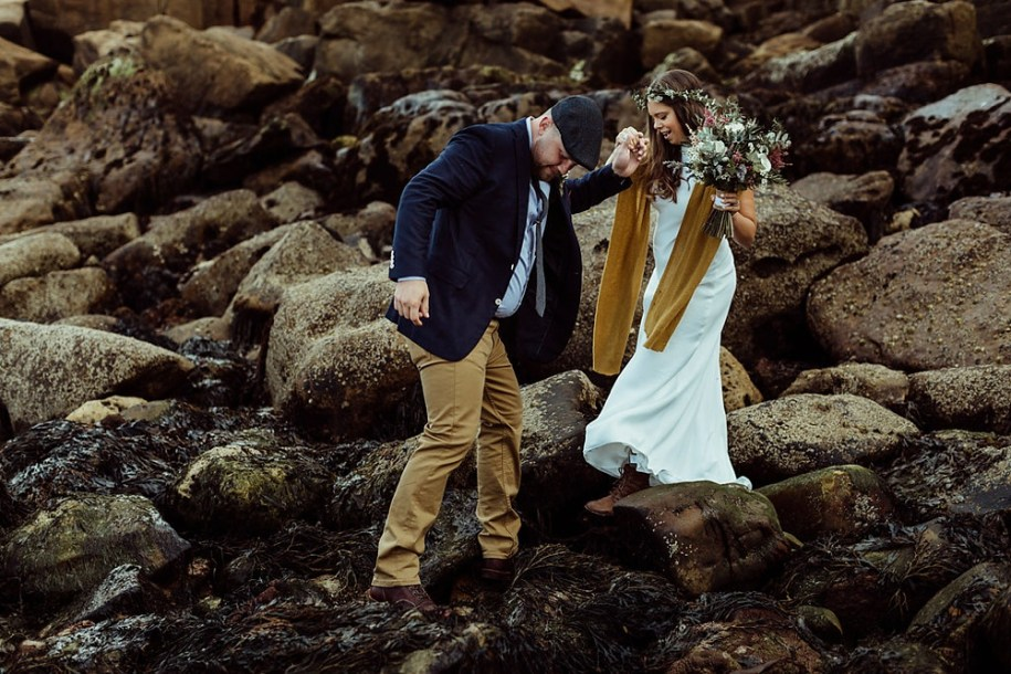groom helping bride to walk down the rocks during their portrait shoot
