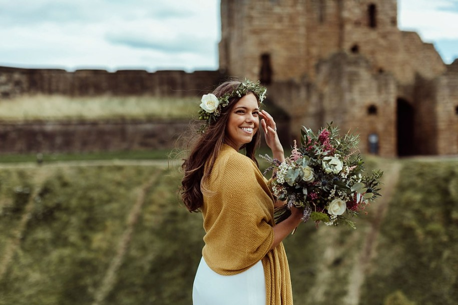 boho bride holding with citadel behind in Tynemouth