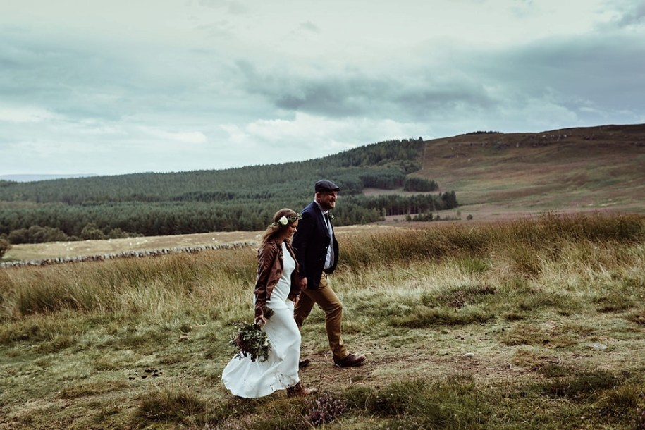 bride and groom walking up the hill in northumberland