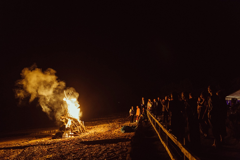 wedding guests by bonfire on the sea shore