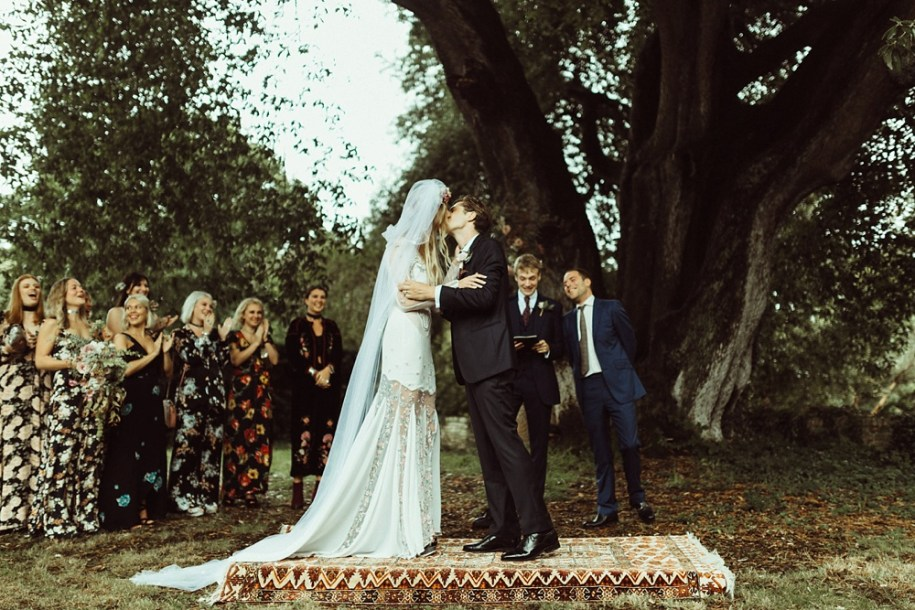bride and groom kiss during their outdoor wedding ceremony in New Forest