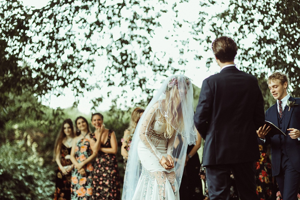 bride laughing during the outdoor wedding ceremony in New Forest , England
