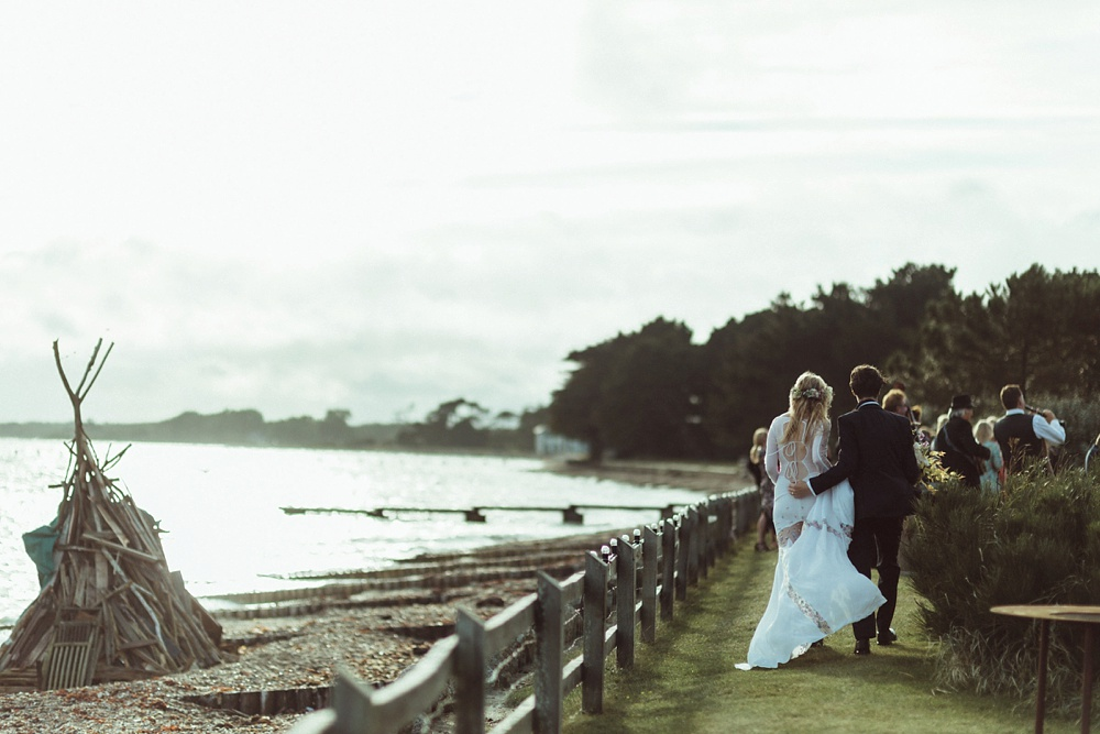 bride and groom walking on the sea shore in New Forest England