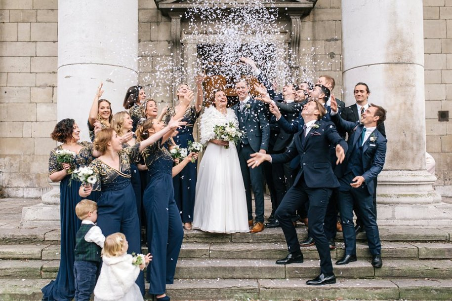 bridesmaids dressed in navy blue throwing paper confetti on the bride and groom whilst standing on the churches stairs