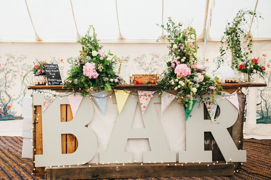 bar area with flowers for marquee wedding
