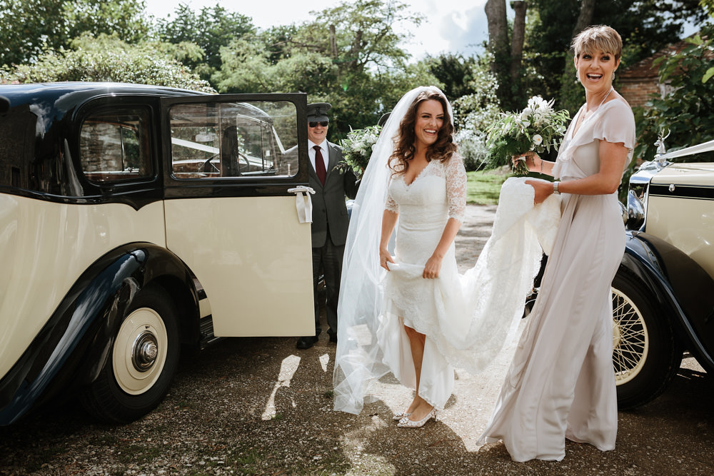bride and bridesmaids getting into vintage Rolls Royce