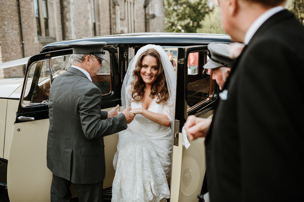 bride coming out of rolls royce for her wedding