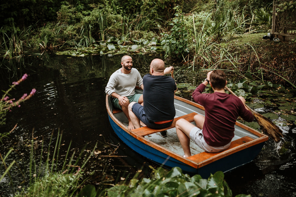 groom and groomsmen on boat in the morning of wedding