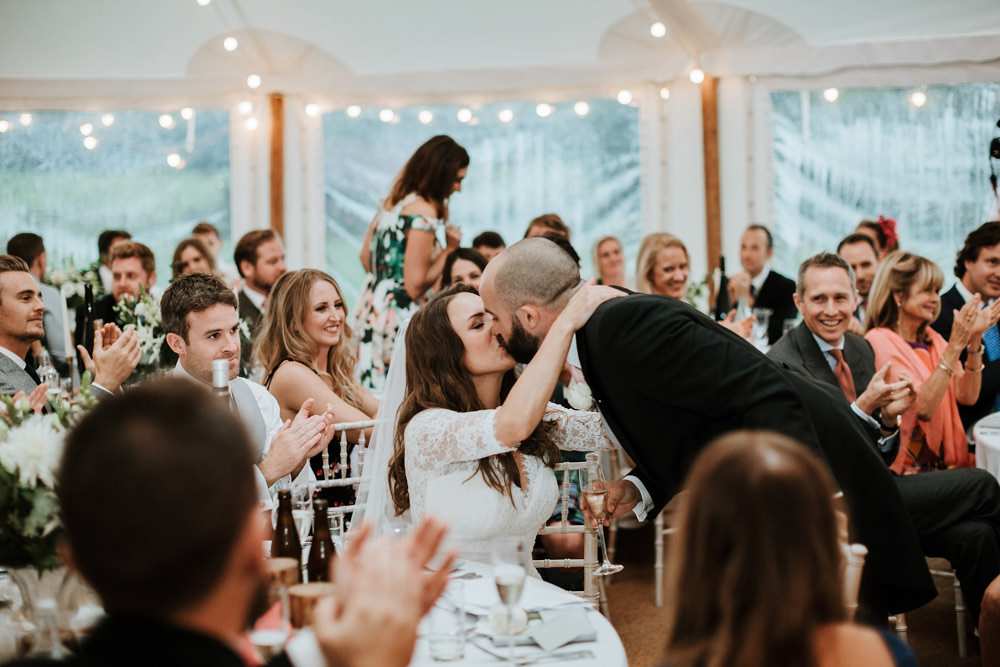 bride and groom kissing during wedding speeches
