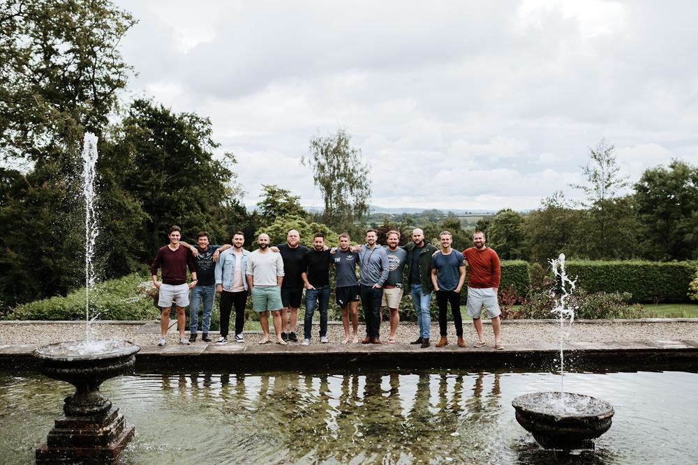 groomsmen group photo by pool in dorset