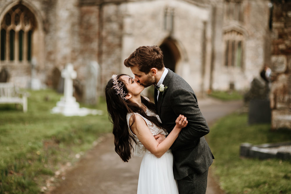 bride and groom kiss outside church after their Bristol wedding ceremony