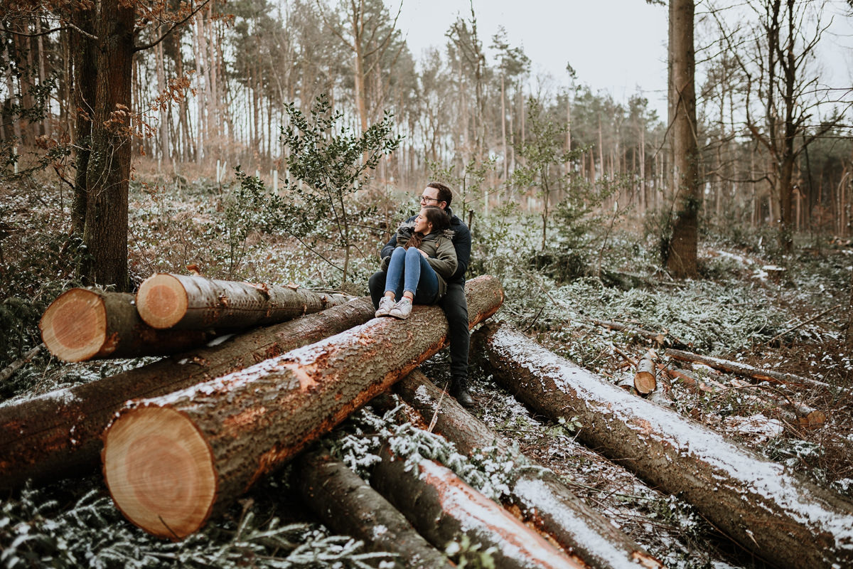 engaged couple posing on long fallen logs in Wyre Forest