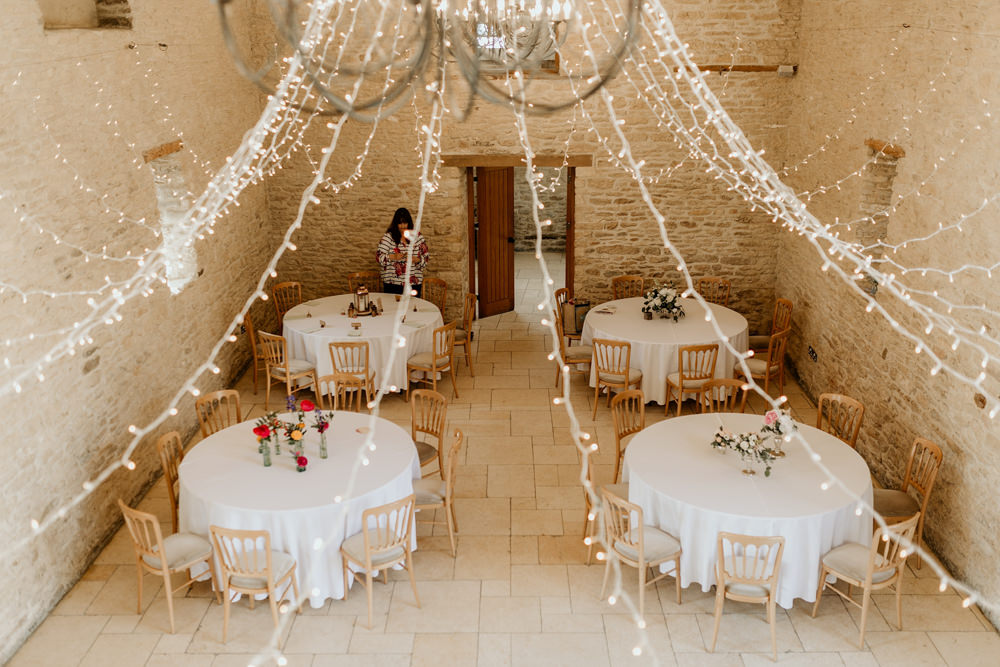 round tables and fairy lights inside The Kingscote Barn Wedding venue by Cotswolds wedding photographer