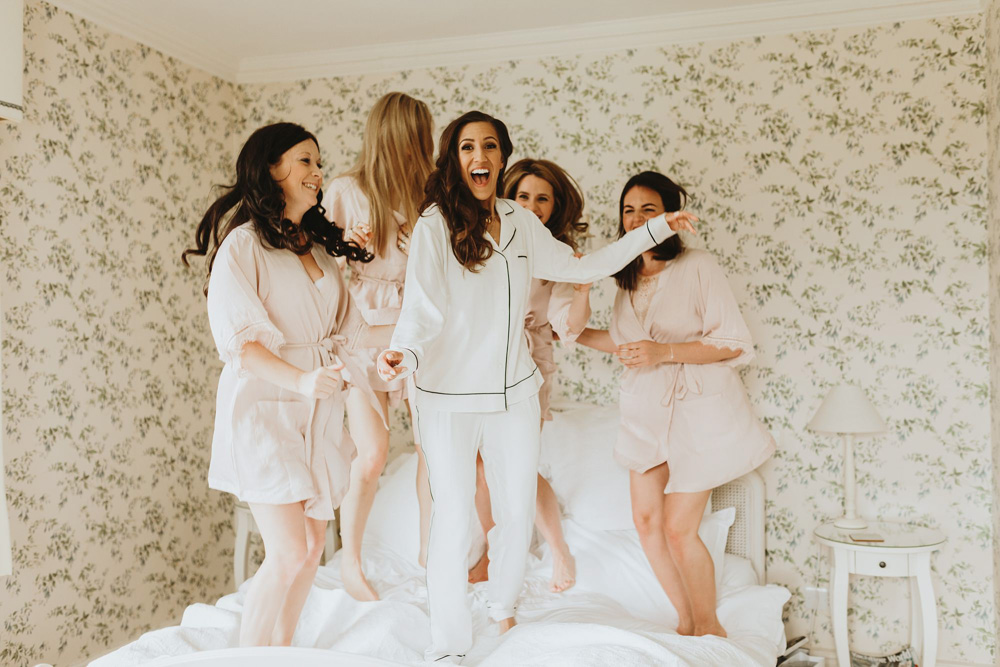 bride and bridesmaids jumping on bed at Plas Dinam Country House