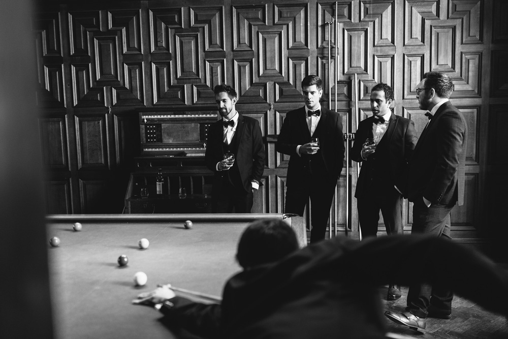 black and white image of groomsmen playing pools before the wedding