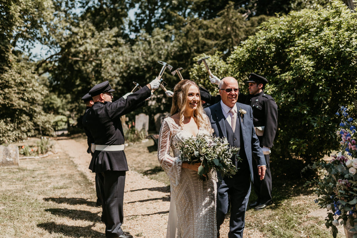 bride walking through tunnel made by firemen with her father by Canterbury wedding photographers Green Antlers Photography