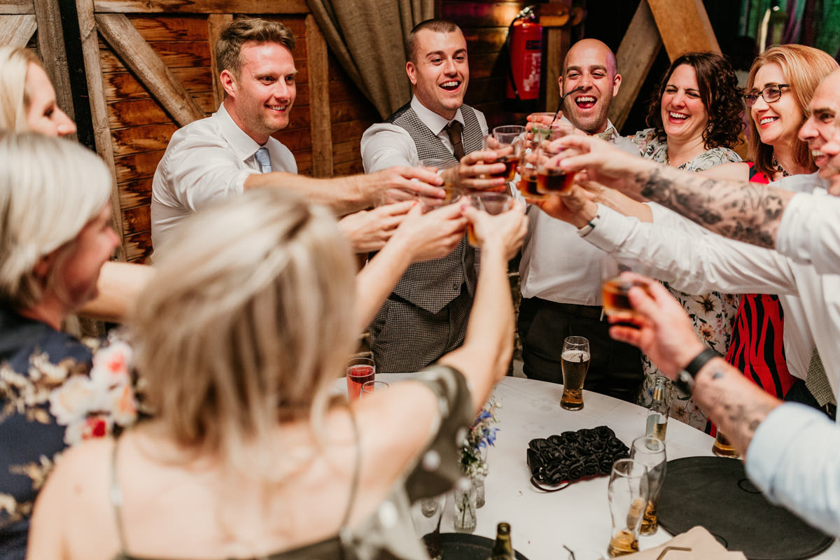guests having shots during the reception at preston court wedding venue by Canterbury wedding photographers