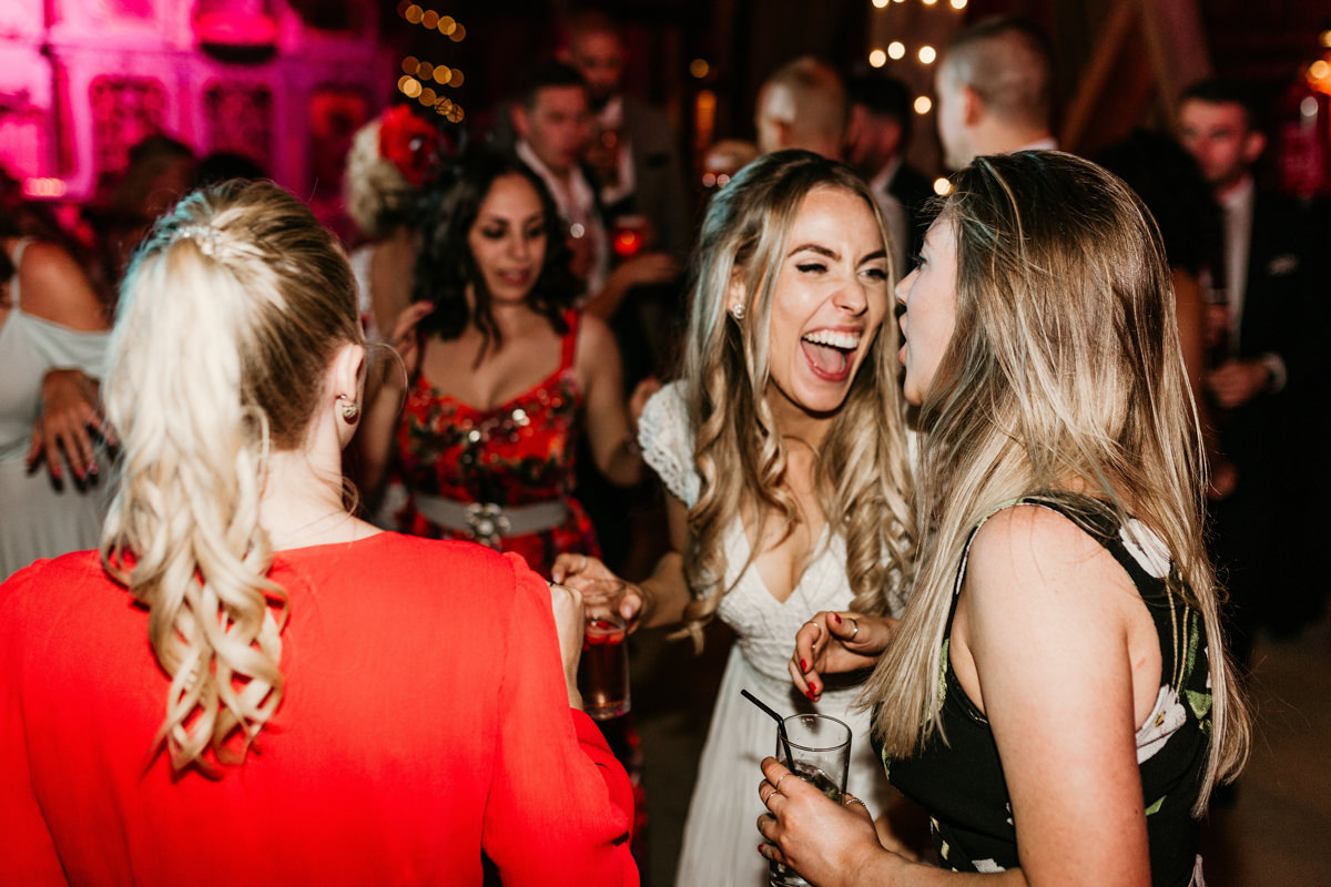 bride laughing with guests at preston court wedding venue by Canterbury wedding photographers