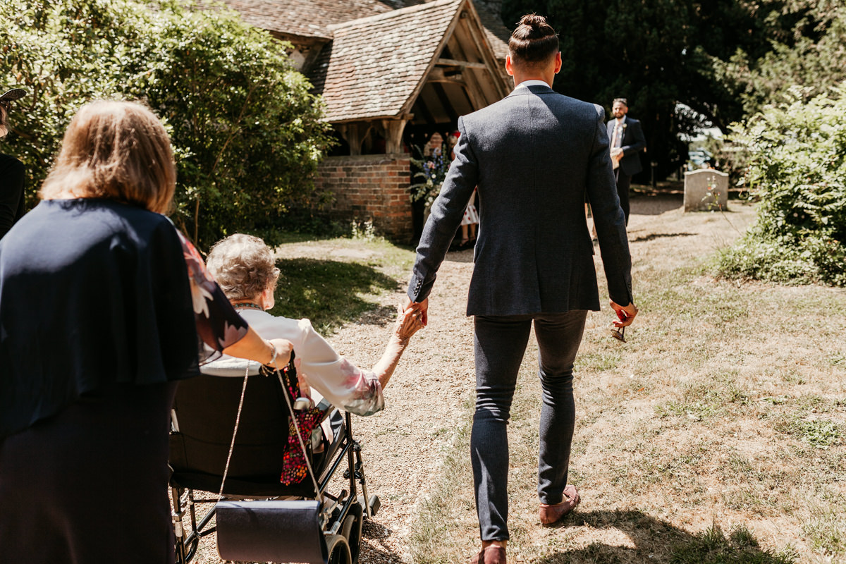 guests going to church for the wedding ceremony by Canterbury wedding photographers