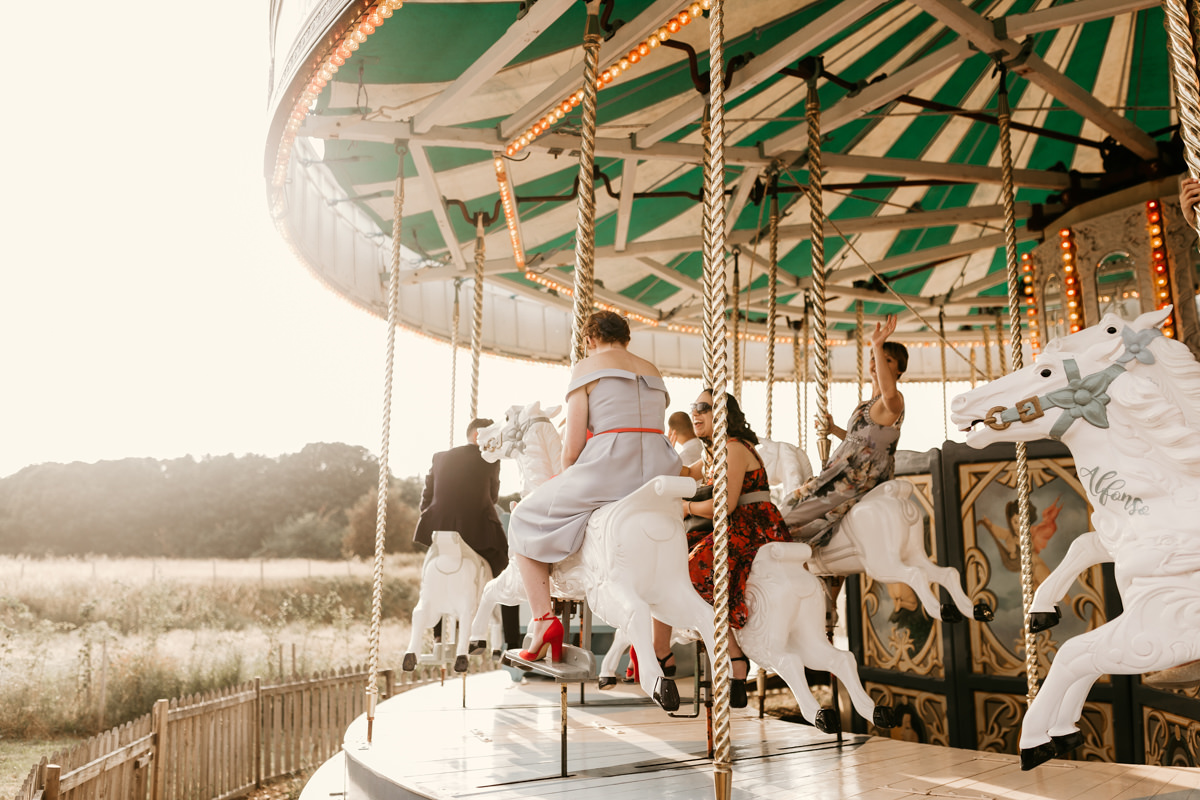 guests having fun on the carousel during the wedding reception at preston court wedding venue by Canterbury wedding photographers