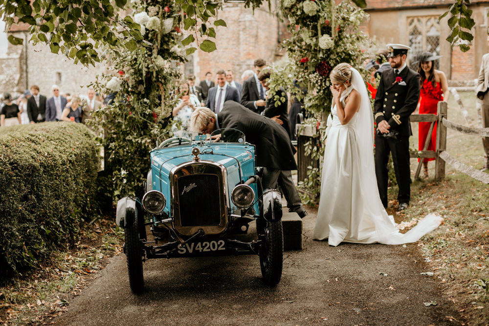 bride and groom after church in their blue Austin 7 Ulster vintage car