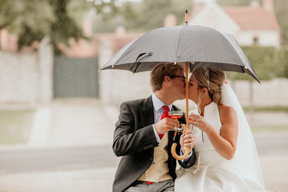 bride and groom kiss in the rain under umbrella at Country house venue wedding | The Kennels Goodwood