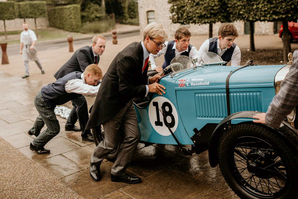 groom pushing a blue Austin 7 Ulster vintage car outside The Kennels Goodwood wedding venue England