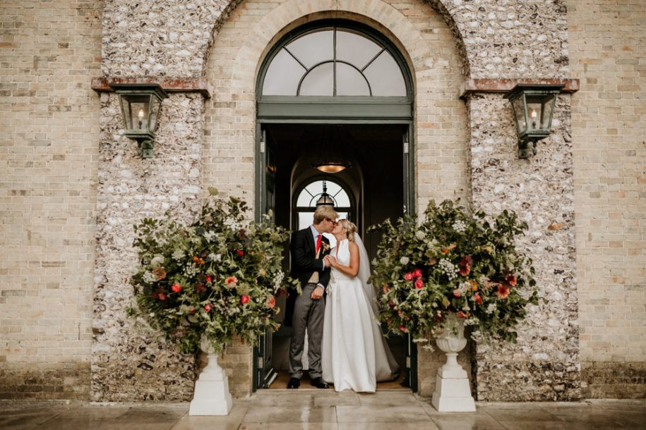 bride and groom kiss in doorway at The Kennels Goodwood wedding venue England
