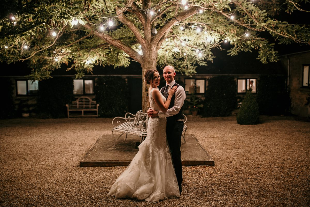 bride and groom under fairy lights tree in the garden of Merriscourt Barn Wedding venue by Cotswolds wedding photographer