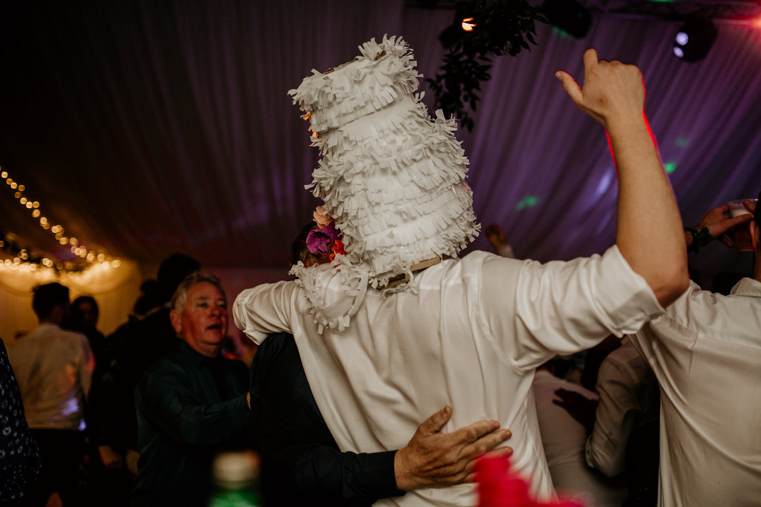 guest during the wedding reception wearing a confetti cake on his head