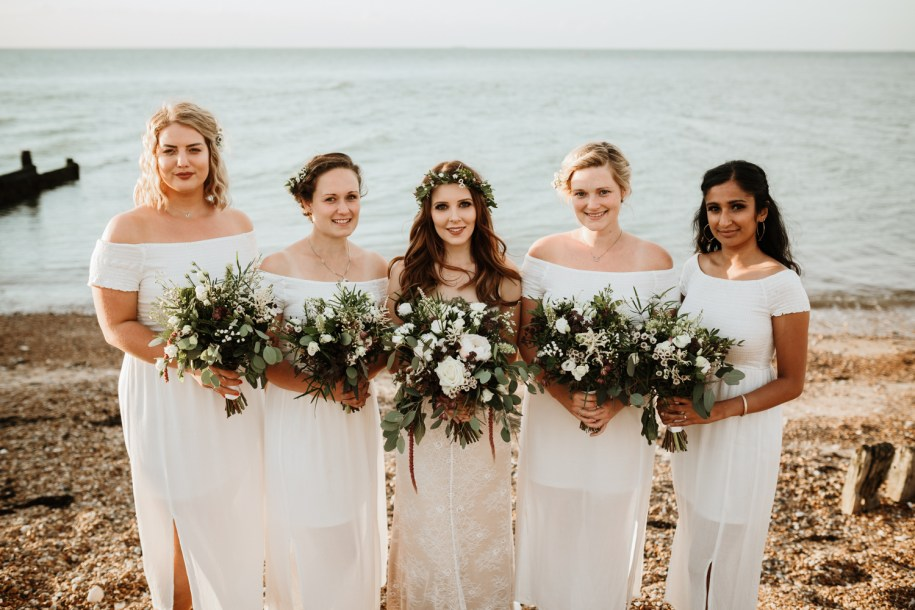 bride and bridesmaids holding a bohemian wedding bouquets on the beach