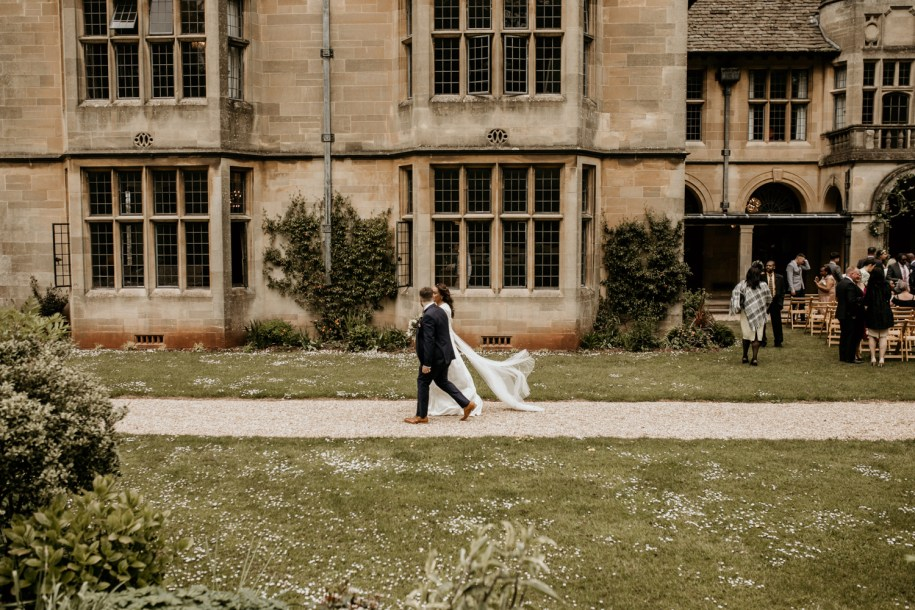 bride and groom walking on the path from their wedding ceremony at Coombe Lodge Blagdon wedding venue