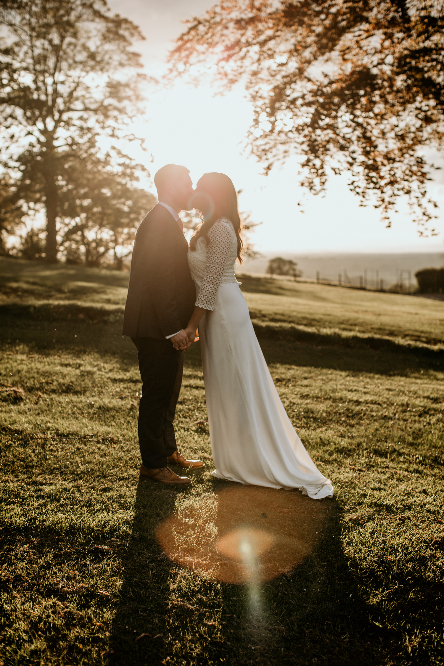 bride and groom kissing during sunset time at Coombe Lodge Blagdon wedding venue